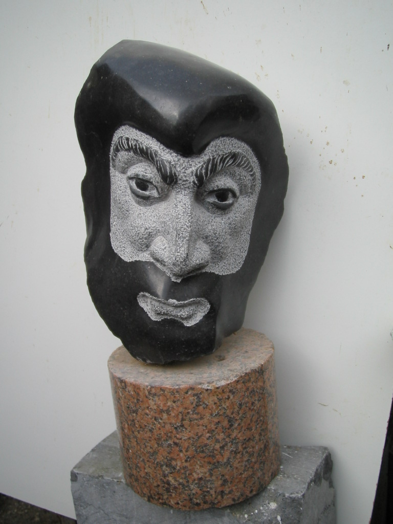Ballad Singer, Limestone. A small head mounted on red granite, inspired by a Wexford singer.