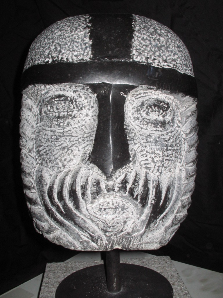 Norman Head. Limestone. Close up of small head mounted on  metal stand.